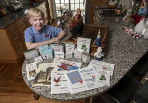 Roberta Mudge Humble, with the many Rhode Island-themed games and books she has created through the years. PBN PHOTO/MICHAEL SALERNO